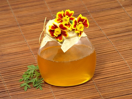 Honey jar and yellow flowers on a wooden surface. photo