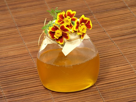 Honey jar and yellow flower on a wooden surface. photo