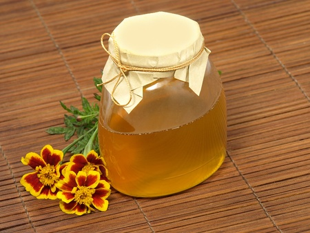 Honey jar and yellow flower. photo
