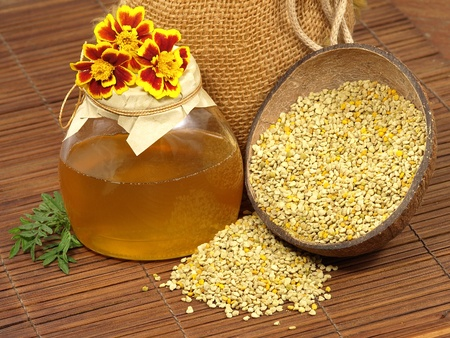 Honey jar,yellow flowers and pollen on a wooden surface. Stock Photo - 11028247