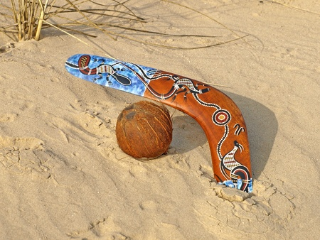 Colorful boomerang and coconut on a sand. photo
