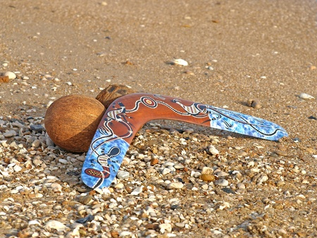 Colorful boomerang and coconut on a sandy beach. photo