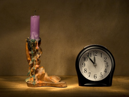 Candle in wooden candlestick and alarm clock on a wooden table.