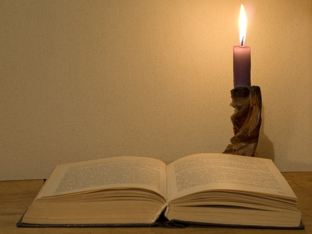 Old open book and  glowing candle on a wooden table. Stock Photo