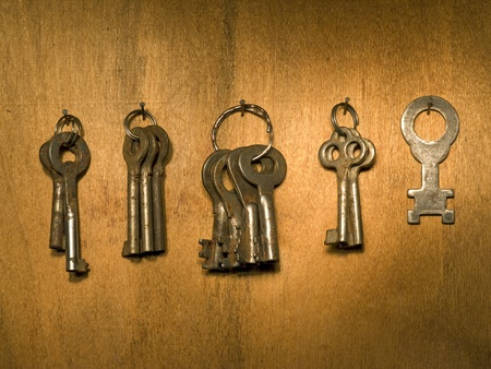 Bunch of old keys on a wooden wall surface. photo