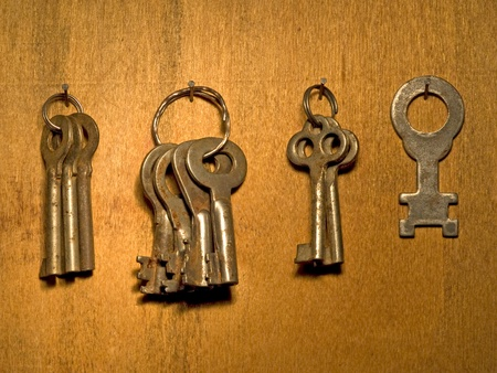 Old keys banch on a wooden wall surface. photo