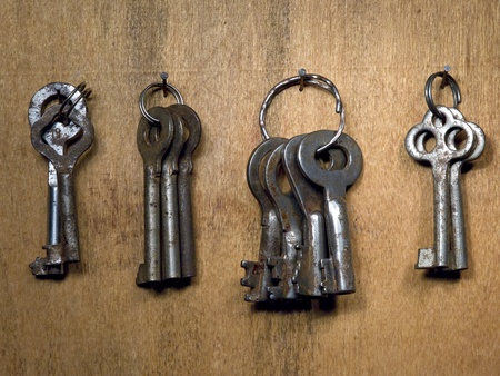 A lot rusty old keys on a wooden wall. photo