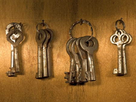 Old rusty keys on a wooden wall. Stock Photo