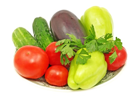 Plate with fresh vegetables isolated on white background. photo