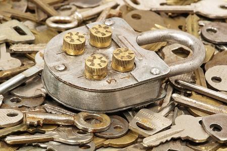 Metal old lock on a lot keys background.