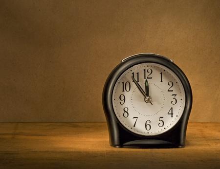 reloj pared: Reloj despertador negro sobre una mesa de madera en la oscuridad.
