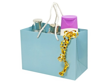 Cosmetic containers  in blue gift bag isolated on white background. photo