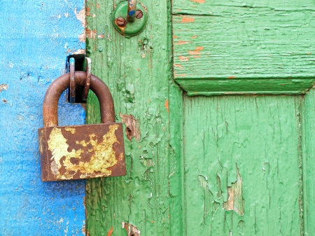 Old metal lock on a aged color wooden door taken closeup. photo