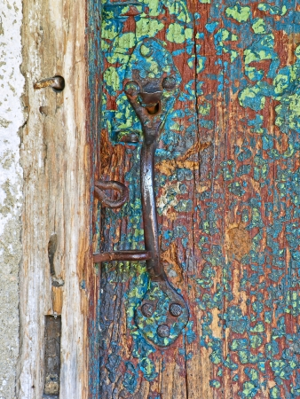 Old wooden door and metal handle taken closeup  photo