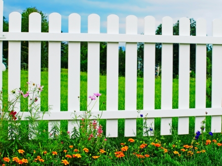 trespass: White wooden fence on green grass with flowers  Stock Photo
