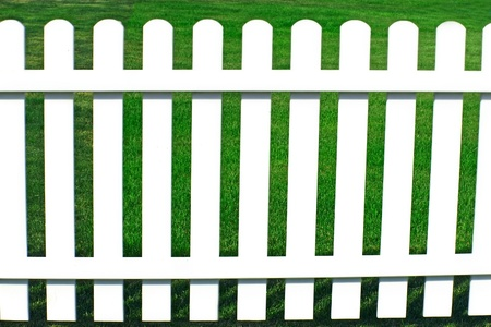 perimeter: Bright green grass on other side behind a white fence