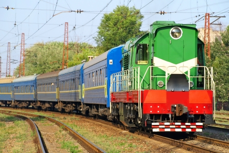 Green locomotive and blue passenger cars on the rails  Stock Photo