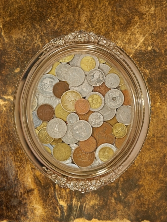 numismatic: Golden oval photo frame with numismatic coins collection inside on grungy wall  Stock Photo