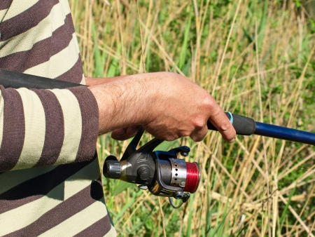 fishingline: Hands of a fisherman with spinning rod on a river taken closeup.