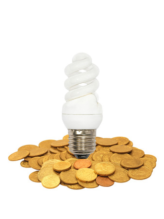 socle: Energy save lamp and coins heap isolated on white background. Stock Photo