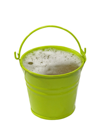Green bucket with foaming liquid isolated on white background. photo
