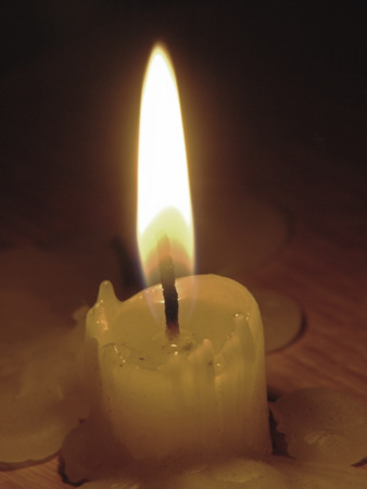 Glowing mourning candle on wooden table in a darkness.