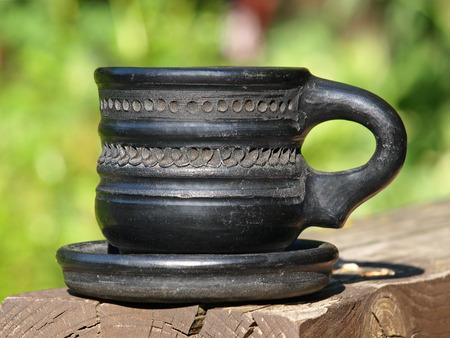 loamy: Old black arabian ceramic cup taken closeup on green background.
