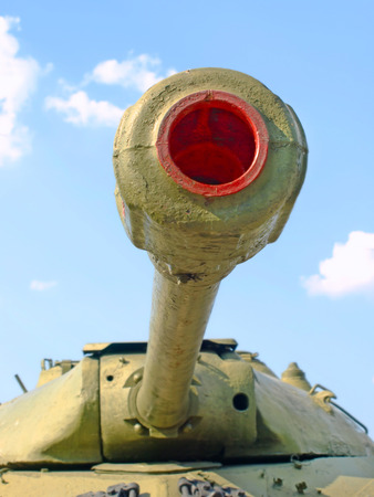 firepower: Military tank cannon against of the blue sky taken closeup. Stock Photo