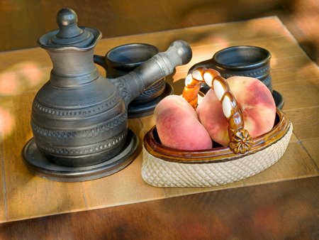 loamy: Coffee set and ceramic vase with peaches on a table
