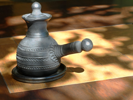 loamy: Arabian style coffee pot on wooden table. Stock Photo