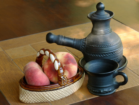 loamy: Arabian coffee pot and ceramic vase with peaches on a table. Stock Photo