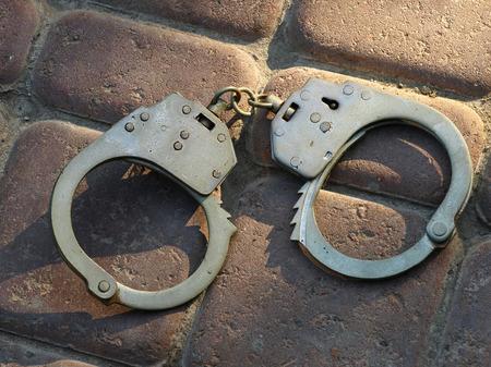 Handcuffs taken closeup on a stone floor. photo