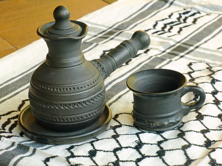 loamy: Ceramic coffeepot and cup on a white keffiyah scarf taken closeup. Stock Photo