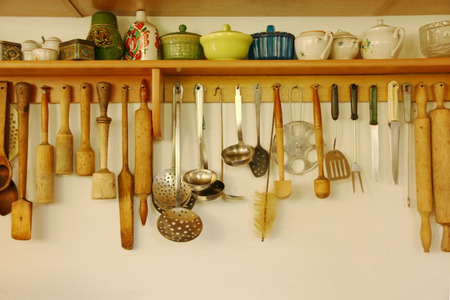 cooking ware: Kitchen ware hanging on the white wall.