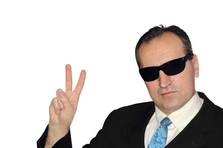 Man in black showing the victory sign on while background.