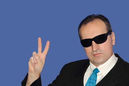 winning bid: Man in black showing the victory sign on blue background.