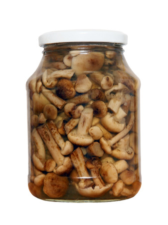 tinned: Appetizing tinned mushrooms in glass jar isolated on white background.