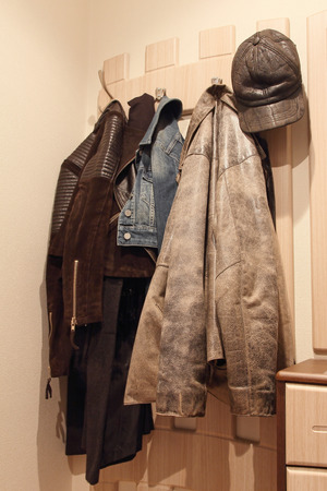 coat rack: Various clothes hanging on a wooden coat rack.