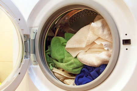 laundry detergent: Clothes inside of washing machine taken closeup.