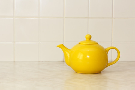 loamy: Yellow ceramic teapot on white kitchen table and ceramic tile background.