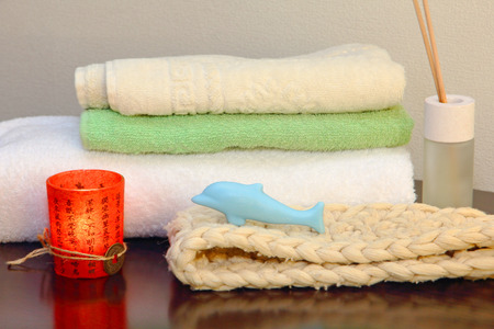terrycloth: Towel stack with bast and dolphin form soap in the shower.