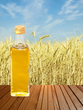 Vegetable oil on wooden surface against of yellow wheat ears and blue sky. photo
