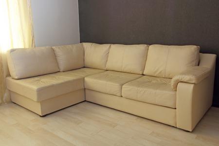 Modern beige corner leather sofa in livingroom.