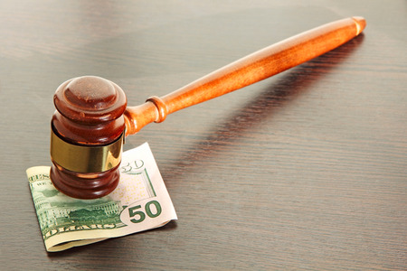 Judge gavel and fifty dollars on wooden table taken closeup.