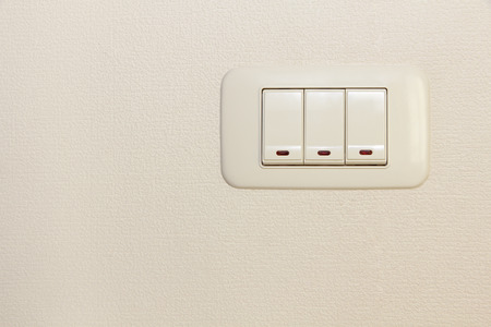 threefold: Threefold multiply light switch on white wall background.