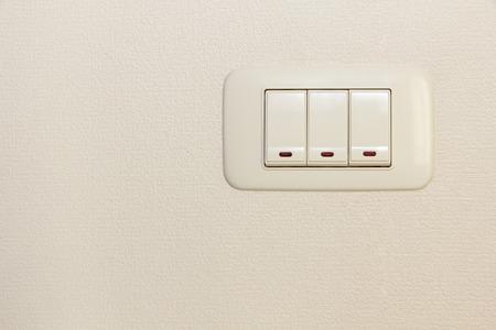 multiplicar: Triple multiplicar interruptor de luz en la pared de fondo blanco.