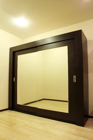 Huge mirror wardrobe in beige tone room taken closeup. Stock Photo