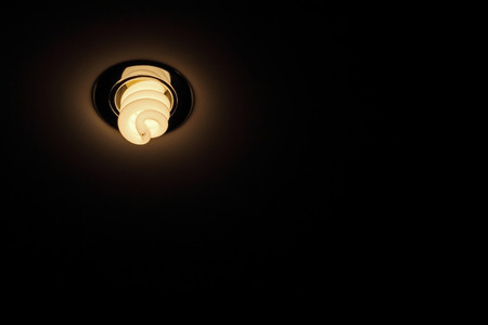 eficiencia energetica: La energía salva la lámpara en el techo tomada de cerca en la oscuridad.