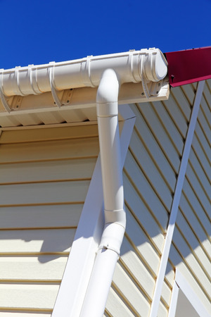 overhang: New plastic rain gutter system with drainpipe on white wall taken closeup. Stock Photo