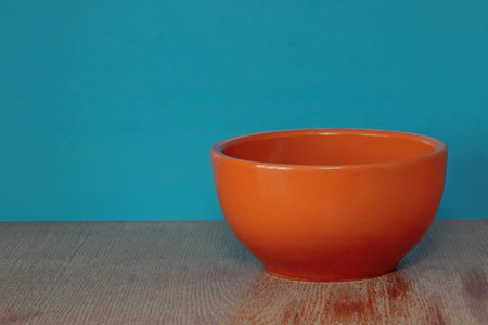tureen: Ceramic plate, soup tureen on wooden surface against of blue background taken closeup. Stock Photo